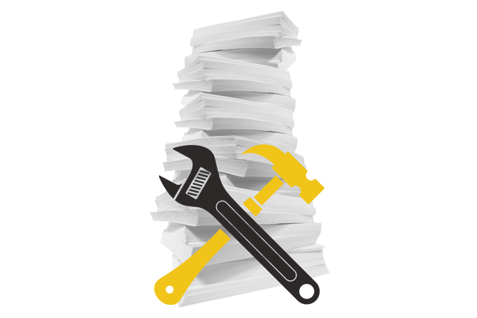 A stack of paper with a crossed wrench and hammer in front