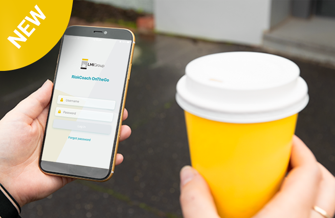 RiskCoach OTG being used outside of an office with a coffee in hand.